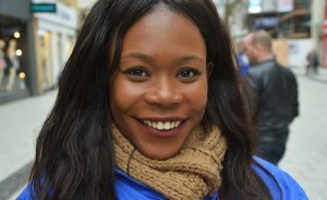 african american woman smiling wearing brown scarf